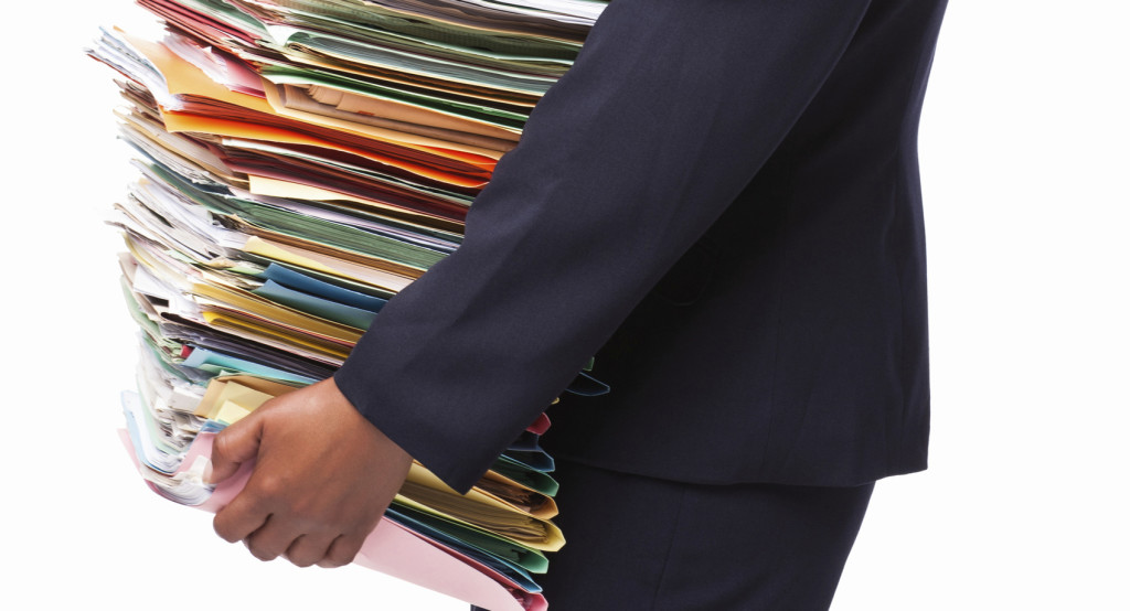 portrait-of-an-african-american-businesswoman-full-of-work-holding-a-pile-of-filing-documents-vertical-shot-isolated-on-white-2